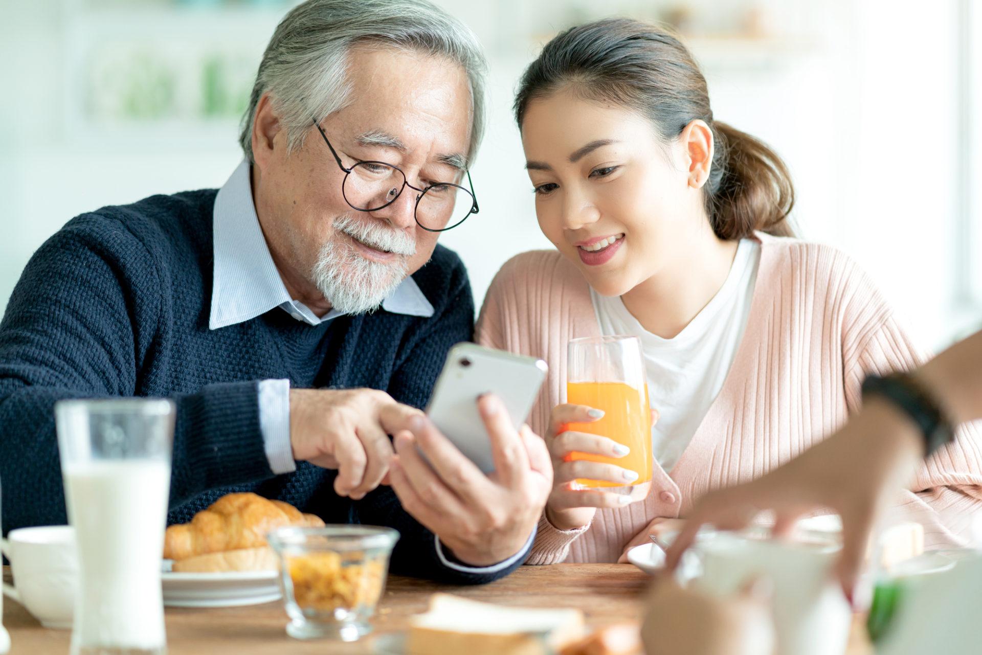 孫とスマートフォンを見るシニア