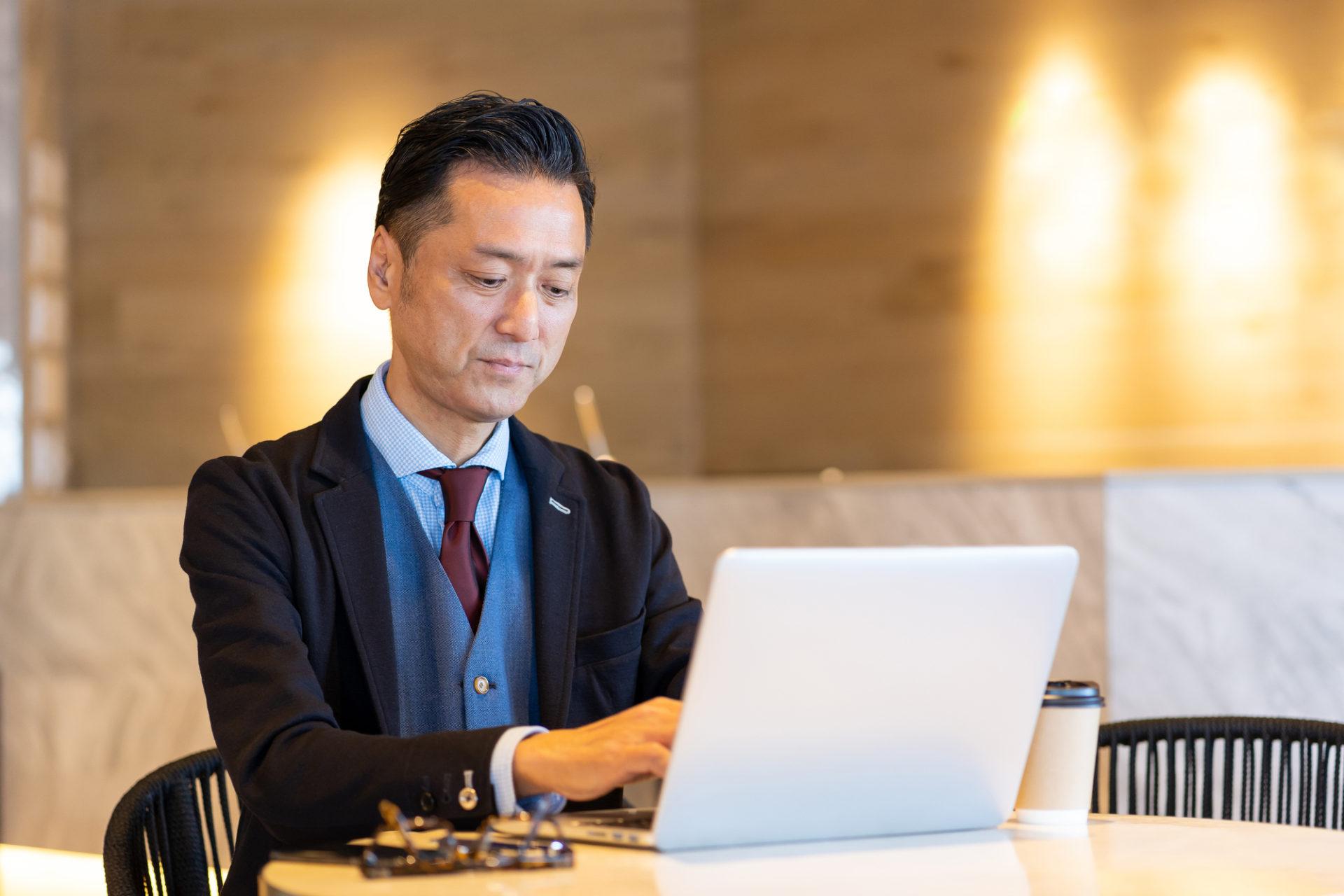 パソコンでプログラミングするシニア男性