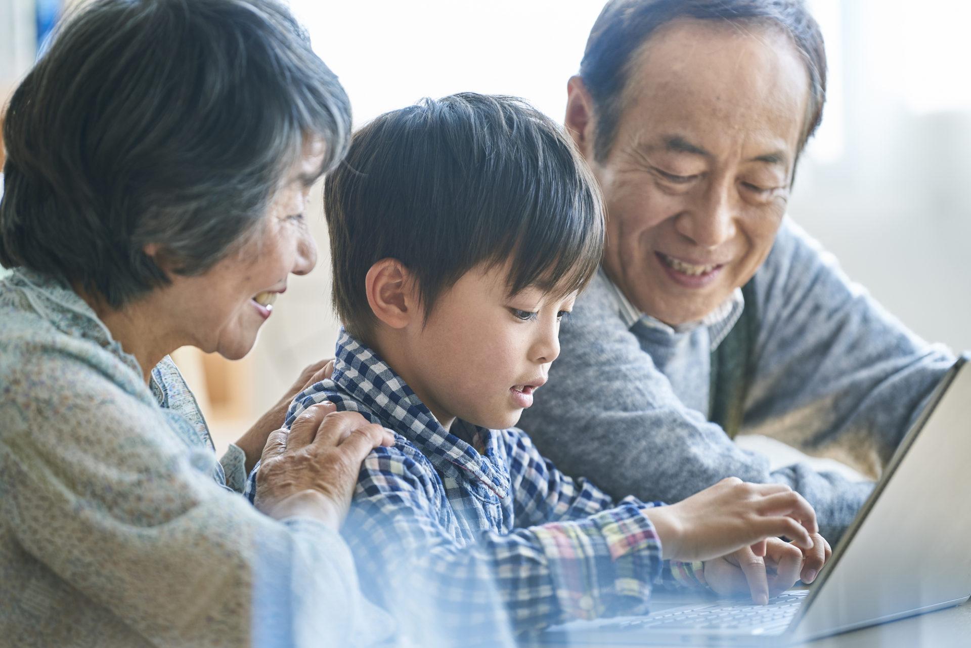 孫にプログラミングを教える祖父と祖母